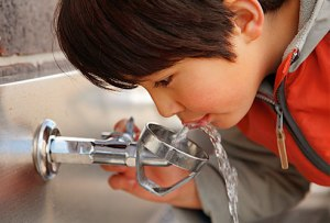child drinking from faucet